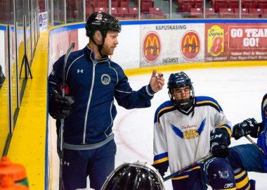 Un des entraineurs des flyers qui explique à ses joueurs sur la glace quelques stratégies