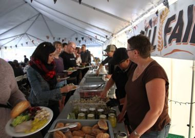 People are served buffet-style under a tent.