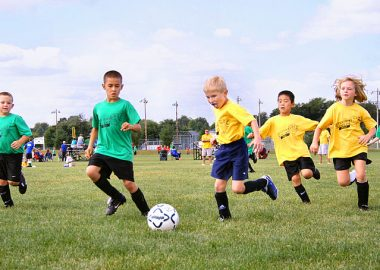Kids in yellow and green jerseys chase the soccer ball on a green field.