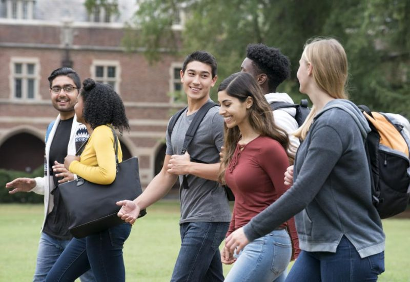 College students are walking outside on their way to their next class.