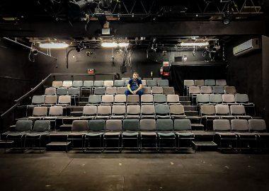 Matthew Downey, directeur technique du Bus Stop Theater, assis dans la salle vide du théâtre. Photo : Bus Stop Theater