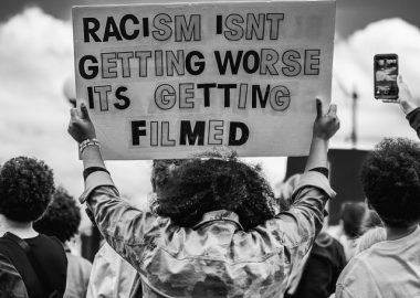 A black-and-white image of the back of a person in a crowd, holding a sign over their head that says