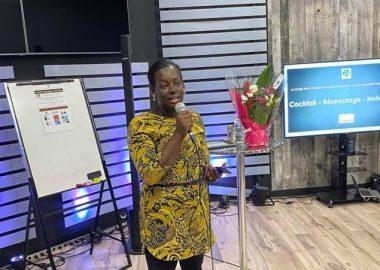 La présidente du Conseil de la Communauté Noire de Gatineau, Aïchatou Touré présente un projet dans une salle de conférence, micro à la main.