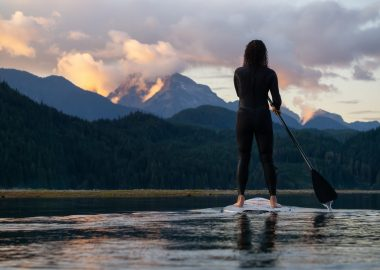A person a paddle board at sunset with mountains in the background