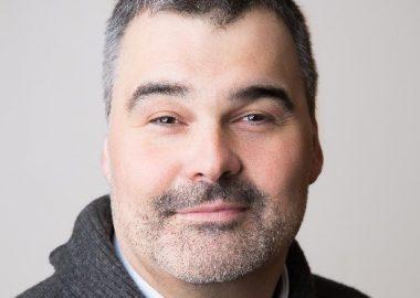 Alain Boisvert, souriant, vêtu d'une chemise et d'un chandail en laine