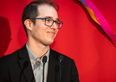 Monsieur Alexandre Leduc vêtu d'une veste noire sur chemise grise, devant un fond rouge