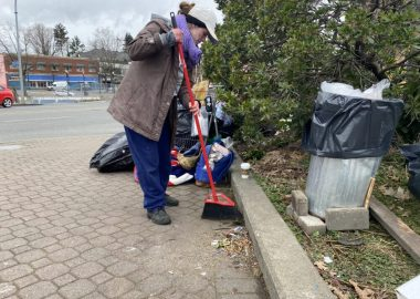 Photo of a woman sweeping a sidewalk with a garbage can beside her and her belongings in bags behind her.