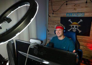 Alsenic assit devant ses écrans d'ordinateur. Un drapeau de pirate est accroché derrière lui.
