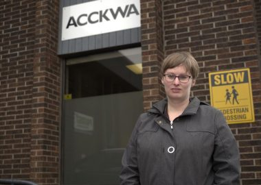 Amy Veener, with glasses and wearing a coat, stands in front of a brown brick building, with a sign reading