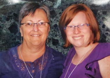 Deux femmes vêtues de mauve sur fond gris.
