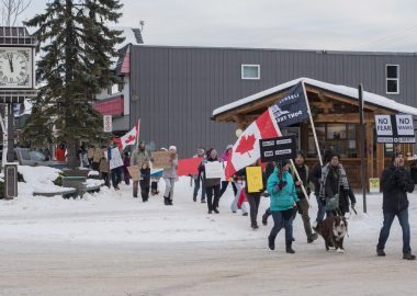 A group of people walk with flags to protest wearing masks in downtown Smithers
