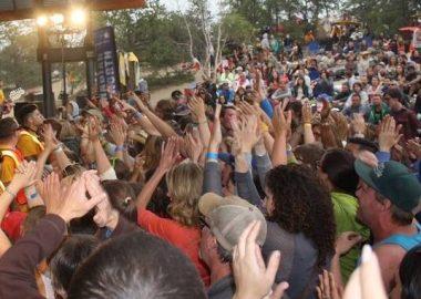 Une foule aux mains agitées regarde un concert.