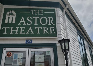 Sign for the Astor Theatre above glass double-doors in a white building