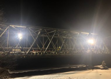 A bridge at night with trouble lights on as engineers and workers assess the damage.