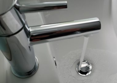 A bathroom tap pours water into sink