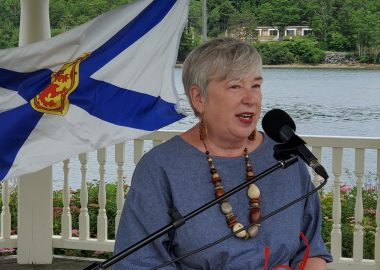 A woman speaks at podium in front of the ocean. A Nova Scotia flag flies behind her.