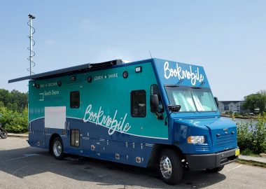 A large blue truck with Bookmobile written along sthe side is parked in front of the ocean