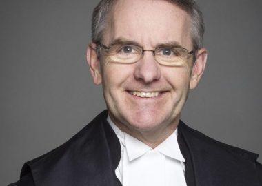 Bruce Stanton souriant devant un fond gris