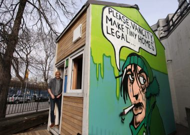 Bryn Davidson stands outside of a wooden tiny home with an artwork painted on the side featuring a man smoking against a green background