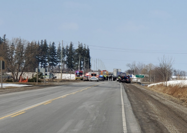 Emergency crews are seen at a distance on Highway 7 on a sunny day