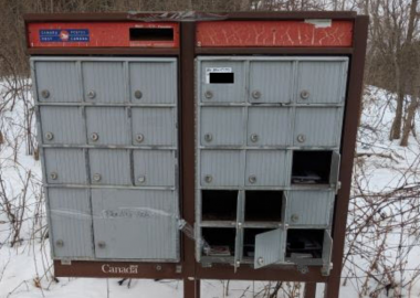 A picture of a damaged Canada Post mailbox against a snow-covered background.