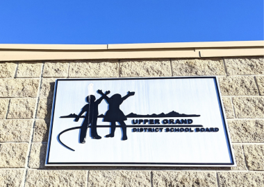 The Upper Grand District School Board logo on a sign, attached to a building