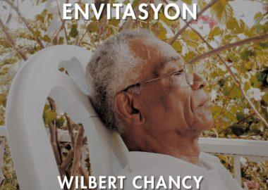 Wilbert Chancy, yeux fermés et lunettes, cheveux grisonnants, assis dans son jardin à Jacmel