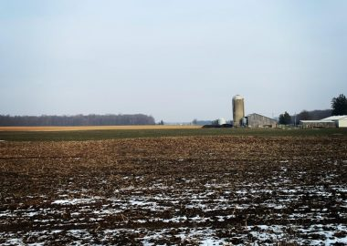 Snow and soil in the foreground of a picture which leads though a farm field, past a silo and barn, and into the blue sky.