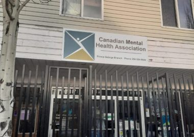 The image shows a barred store front with a sign for the Canadian Mental Health Association, Prince George branch.