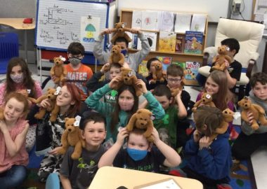 A group of elementary school kids hold identical teddy bears and smile.
