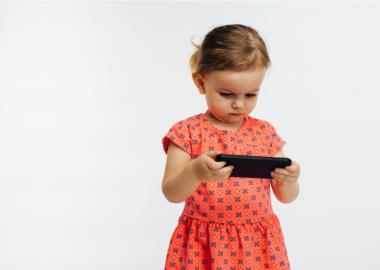 Une petite fille tient fixement un smartphone dont l'image la captive
