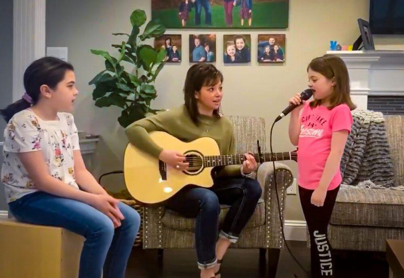 Trois jeunes filles jouent de la musique dans un salon