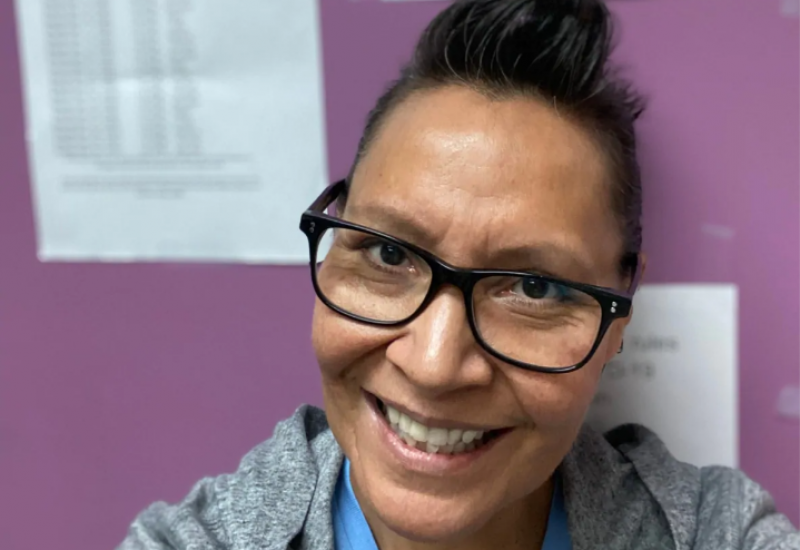 A picture of Tracey Draper, program Coordinator with the Western Aboriginal Harm Reduction Society, against a purple office wall