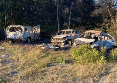 Three burned out cars in a field