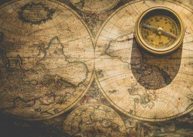 Une vieille carte du onde sur laquelle est posée une vieille boussole