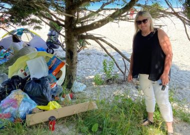 A photo of Queens-Shelburne MLA Kim Masland stands next to a pile of garbage at Carters Beach.