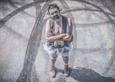 Cédric Vieno dans un stationnement marqué de traces de pneu. Il est vêtu d'un costume de ballerine rurale.