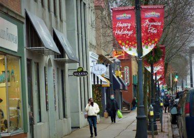 Un lampadaire avec des affiches souhaitant un joyeux Noël en français et en anglais; une femme parlant au téléphone marche sur le trottoir; plusieurs commerces sont à sa droite