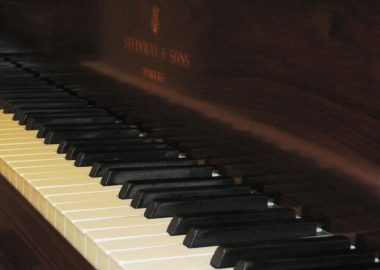 A picture of keys on a dark wooden piano