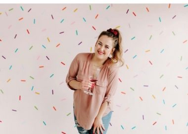 A photo of Bon Apatreat bakery owner Chantelle Villeneuve. Sh is centered in the photo, wearing a pinkish tshirt, blue jeans, a red bow in her high pony tail which matches her lipstick and the wine in the glass she is holding. The background is all confetti.