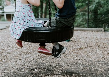 Children's legs dangle off of a tire swing as they sit on it, with a schoolyard in the background.