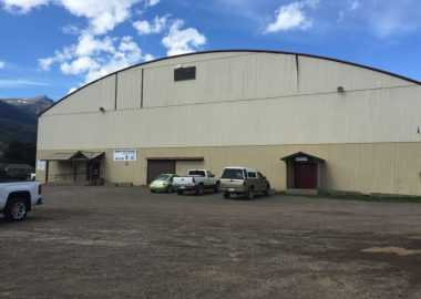 A large building, the back of the arena in Smithers British Columbia on a blue day with a couple of trucks parked in the parking lot.