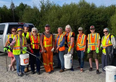 A photo of volunteer clean up crew by the side of the road.