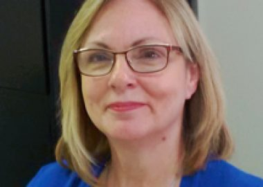 A headshot of Colleen Lariviere wearing a blue top and glasses.