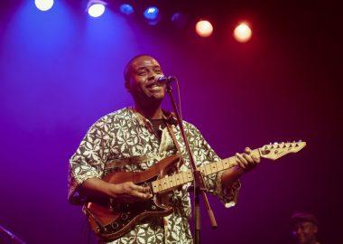 Zekhul en tenue africaine en spectacle jouant à la guitare