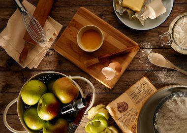 Plusieurs articles de cuisine sur une table avec ddes pommes et du beurre