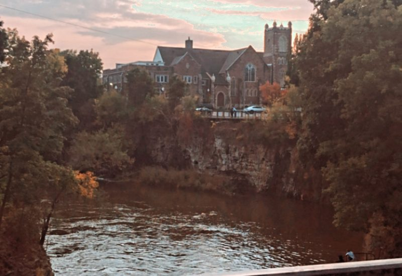 The Grand River is seen from a bridge at sunset in Wellington County with buildings in the distance.