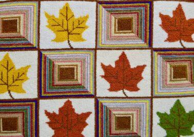 TYapisserie en laine avec feuilles d'érable jaunes, rouges et vertes.