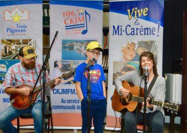Un homme assis jouant de la mandoline, un jeune garçon debout chantant au micro et une dame assis jouant de la guitare.