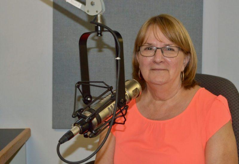 Dame avec cheveux bruns, lunettes et chandail orange au micro d'une radio.